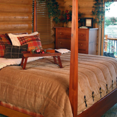 rustic bedroom in log cabin with wood furnishings