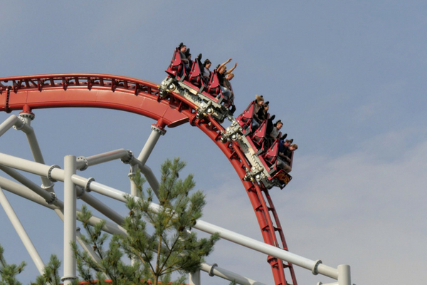 people raise their hands on rollercoaster before making a steep descent