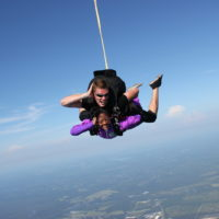 woman & instructor make a pose while in skydiving freefall