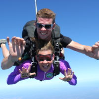 woman skydiving in purple jumpsuit shows writing on hands that says, NEVER BEEN SO HIGH!