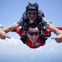 instructor points at first time skydiver in red jumpsuit during freefall
