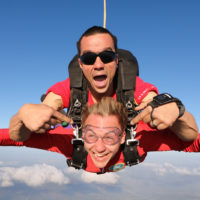 young man smiles widely as he experiences skydiving freefall