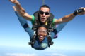 woman grins ear-to-ear in skydiving freefall at Skydive DeLand