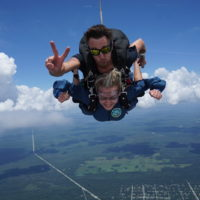 instructor makes peace sign while connected to first time skydiver