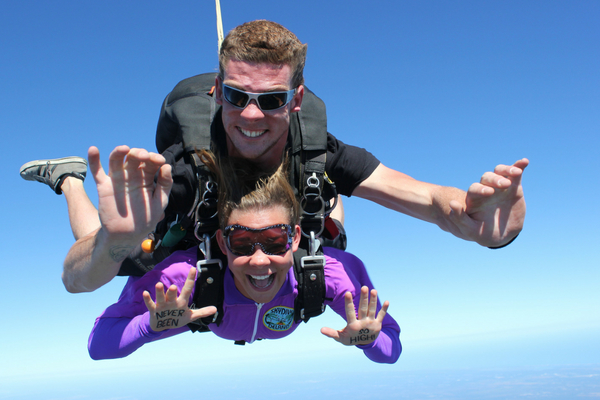woman skydiving in purple jumpsuit shows writing on her hands that says, NEVER BEEN SO HIGH!
