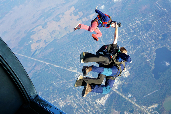 first time skydiver exits plane with instructor and videographer