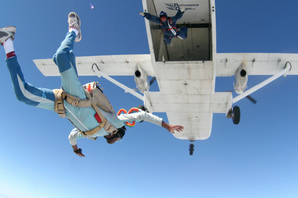 fun jumpers in colorful jumpsuits exit from the SkyVan at Skydive DeLand