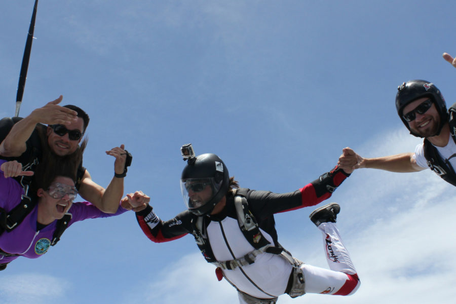 tandem skydiving student safely enjoys freefall attached to instructor