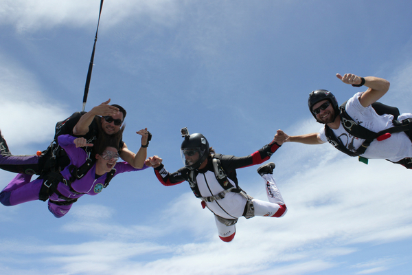 tandem skydiver safely attached to instructor enjoys freefall with 2 other jumpers