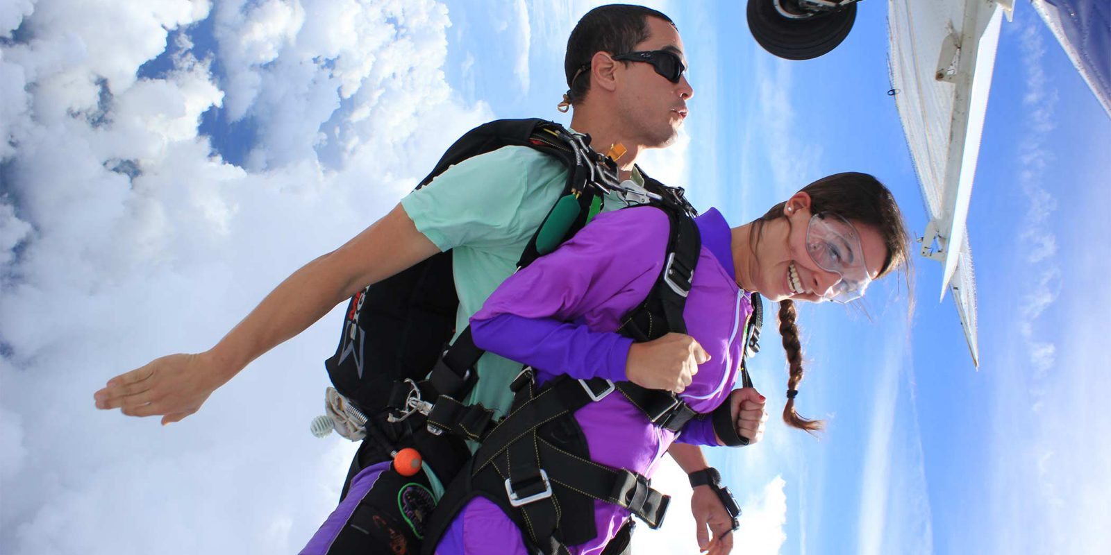 young woman in purple jumpsuit smiles after exiting plane while making her first skydive