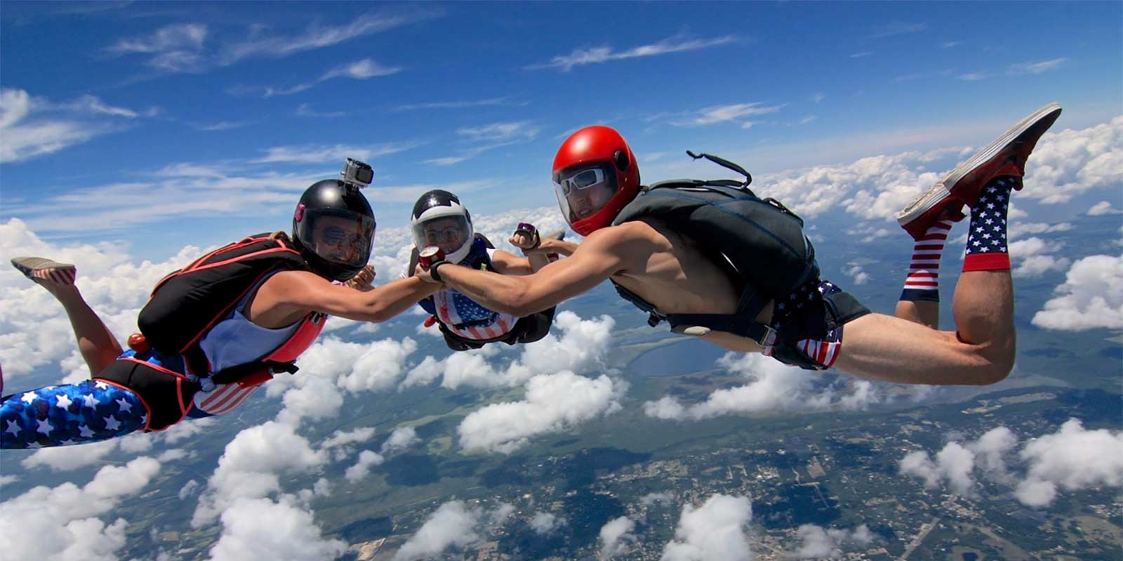 3 fun jumpers in patriotic dress join hands in formation while in skydiving freefall