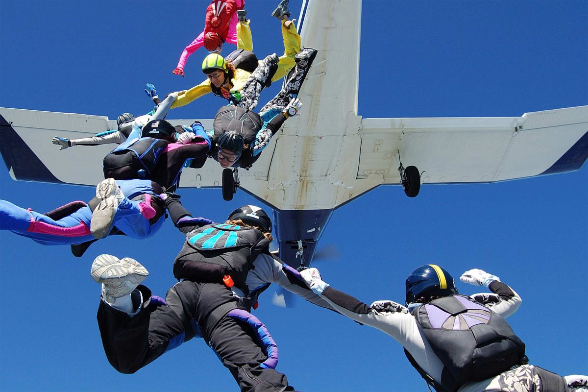 licensed skydivers exit skydiving plane and grab arms