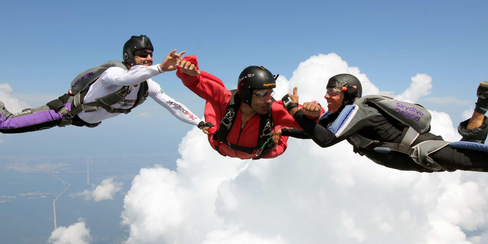 2 instructors hold onto AFF skydiving student while he learns to skydive