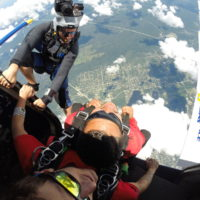first time skydiver poised on the edge of the plane before jumping