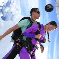 woman in purple jumpsuit smiles at videographer in freefall