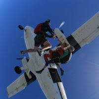 videographer gets close up footage of first time skydiver after exiting plane