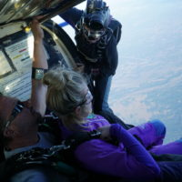 woman sits on the edge of skydiving plane about to jump