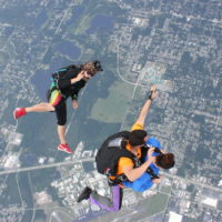 videographer and tandem skydiving pair in freefall