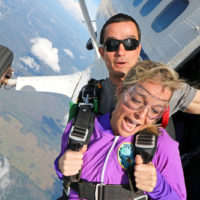 woman looks down after exiting skydiving plane