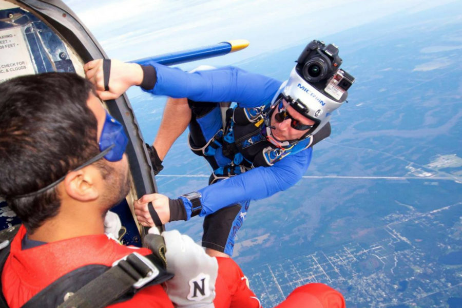tandem skydiver making first skydive sits on the edge of plane with instructor before making the leap