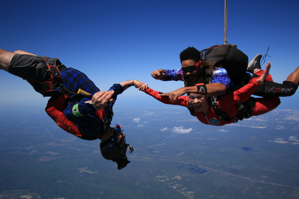 tandem student safely attached to instructor enjoys freefall